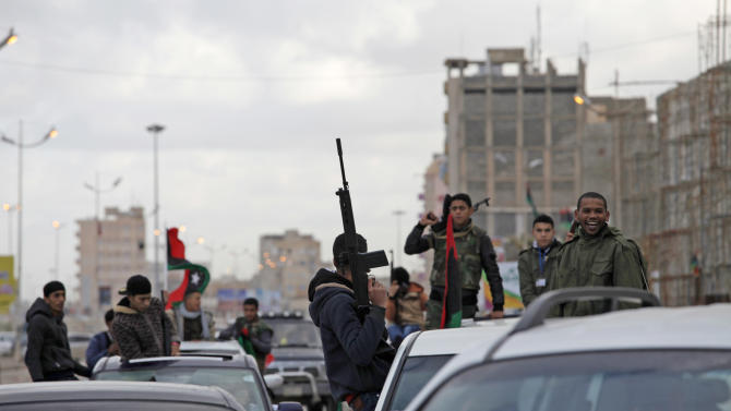 FILE - In this Sunday, Feb. 17, 2013 file photo, Libyan gunmen celebrate on the early morning of the second anniversary of the revolution that ousted Moammar Gadhafi, in Benghazi, Libya. More than 18 months since the end of Libya's civil war, the most attractive job for many of the young is still to join a militia. In fact, just under a tenth of Libya's labor force may be working as gunmen. State coffers are full of cash from rapidly reviving oil production, but rather than funding reconstruction, much of the money goes to buying off a restive population with state salaries, including to militias, effectively feeding a cycle of lawlessness. (AP Photo/Mohammad Hannon, File)