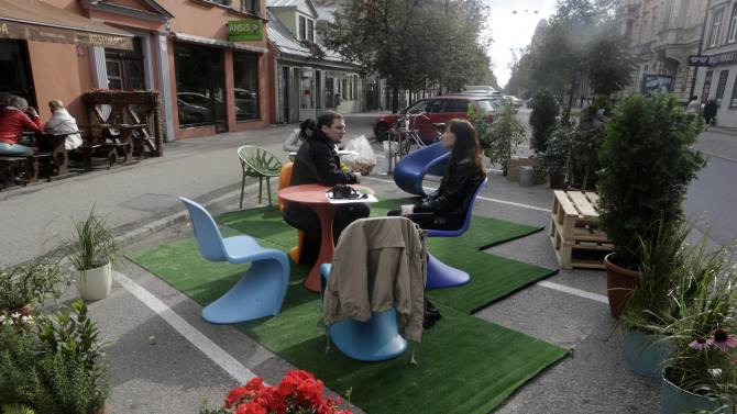 People sit on chairs during a PARK(ing) Day event in Riga