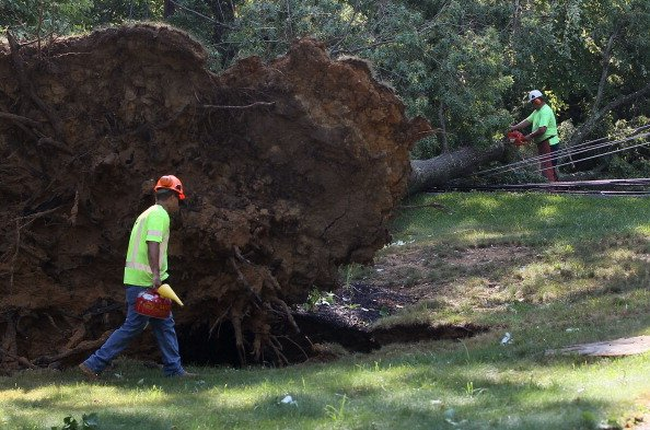 Workers cut up a fallen tree so that power lines can be repaired, on June 30, 2012 in Huntington, Maryland. Over a million homes across the Washington area lost power after a severe thunderstorm hit t