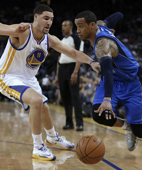 Golden State Warriors' Klay Thompson, left, guards Dallas Mavericks' Monta Ellis during the second half of an NBA basketball game Tuesday, March 11, 2014, in Oakland, Calif. (AP Photo/Ben Marg