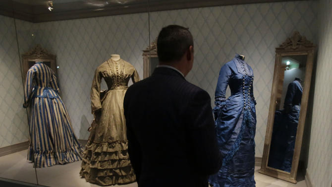"""A journalist looks at women's afternoon  dresses of the 19th century during the press day of the Impressionism and Fashion exhibition in at the Orsay museum in Paris, Friday, Sept. 21, 2012. To coincide with Paris Fashion week, a new and highly original exhibit  called """"Impressionism and Fashion"""" opens at the Musee d'Orsay. It uses famous works of art to explore how at the dawn of impressionism, and as an emblem of """"modernite""""  fashion, and how people dressed, became one of the main themes in art. The exhibition will open September 25, 2012 and last till January 2013. (AP Photo/Michel Euler)"""