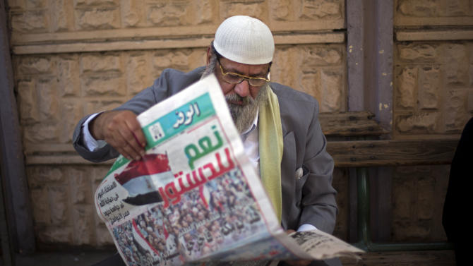 "An Egyptian man reads a local newspaper which has a main headline in Arabic that reads,""yes to the constitution,"" while he waits his turn to cast his vote in the country's constitutional referendum in Cairo, Egypt, Tuesday, Jan. 14, 2014. Upbeat and resentful of the Muslim Brotherhood, Egyptians voted Tuesday on a new constitution in a referendum that will pave the way for a likely presidential run by the nation's top general months after he ousted Islamist President Mohammed Morsi. (AP Photo/Khalil Hamra)"