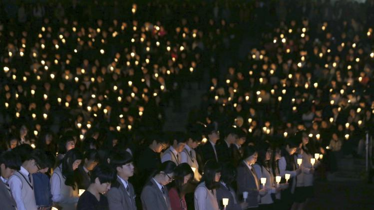 "Students from Danwon high school and other people attend candlelight vigil to wish for safe return of missing passengers from South Korean ferry ""Sewol"", which sank in the sea off Jindo, in Ansan"
