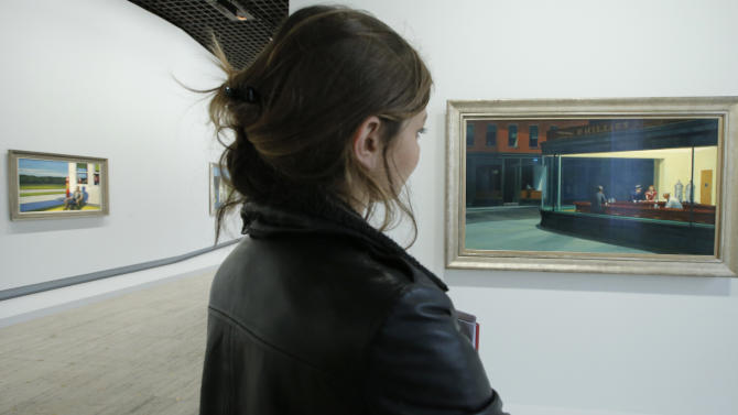 "A woman looks at ""Nighthawks, 1942"", at right, as part of the retrospective of Edward Hopper, one of the great American 20th century artists at Paris' Grand Palais Museum, in Paris, Monday, Oct. 8, 2012.  This major Hopper retrospective reveals that the 20th century painter known for his rendering of American life, also drew inspiration from France, and includes some 128 Hopper works, such as the masterpieces ""Nighthawks"" and ""Soir Bleu"".(AP Photo/Francois Mori)"