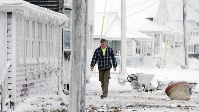 Peadair Flood walks outside his house in Scituate, Mass., Wednesday, Jan. 28, 2015, a day after a winter storm left his neighborhood coated in frozen sea spray and sand. (AP Photo/Michael Dwyer)