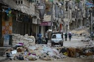 Civilians carry their belongings along a street strewn with garbage and debris following fighting between Syrian government troops and rebel fighters in the Salaheddin district of Aleppo. Syria&#39;s army and main rebel force said they will cease fire on Friday, in line with an internationally backed truce during a Muslim holiday, but both reserved the right to respond to any aggression