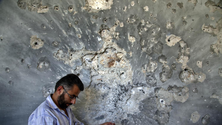 FILE - A Syrian man holds bullets he picked from the wall of a damaged house in the town of Atareb, on the outskirts of Aleppo, Syria, Sunday, Aug. 5, 2012. (AP Photo/Khalil Hamra, File)