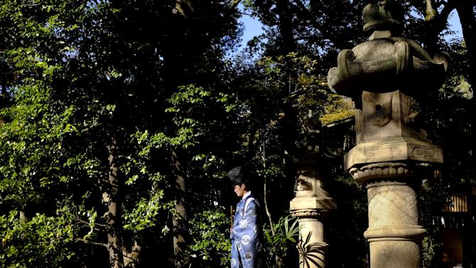 A Shinto priest walks in the garden of the Hikawa shrine during a traditional wedding ceremony in Tokyo