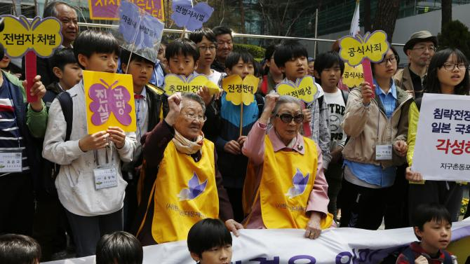 """FILE - In this April 24, 2013 file photo, South Koreans, Kim Bok-dong, center right, and Gil Wen-oak, center left, who were forced to serve for the Japanese Army as sexual slaves, so called """"comfort women,"""" during World War II, shout slogan with their supporters in an anti-Japan protest against the Japanese lawmakers' visit to the Yasukuni Shrine, in front of the Japanese Embassy in Seoul, South Korea. More than 70 years ago, at age 14, Kim Bok-dong was ordered to work by Korea's Japanese occupiers. She was told she was going to a military uniform factory, but ended up at a Japanese-military-run brothel in southern China. (AP Photo/Kin Cheung, File)"""
