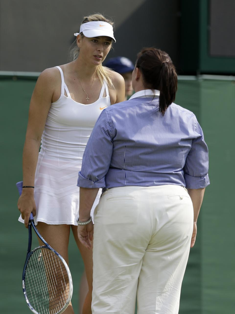 Maria Sharapova of Russia, left, speaks with the umpire during her Women's second round singles match against Michelle Larcher De Brito of Portugal at the All England Lawn Tennis Championships in Wimbledon, London, Wednesday, June 26, 2013. (AP Photo/Anja Niedringhaus)