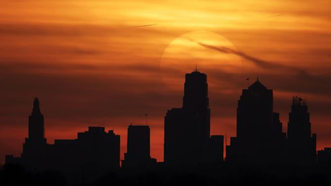 FILE - The sun sets behind the downtown Kansas City, Mo. skyline as above average temperatures returned to the region Thursday, March 14, 2013. Government forecasters say much of the United States can expect a warm spring and persistent drought. The National Weather Service said Thursday, March 21, 2013 above-normal temperatures are predicted across most of the Lower 48 states and northern Alaska. (AP Photo/Charlie Riedel)