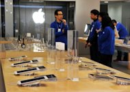 File photo of employees at an Apple store in Tokyo. Apple was seeking 100 million yen ($1.27 million) in compensation from Samsung's Japanese units, and had accused it of stealing technology used to transfer music and video files