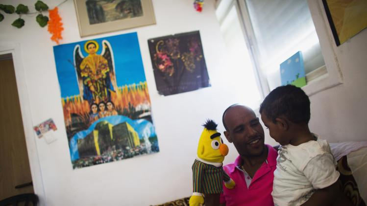 Angesom Solomon, a 28-year-old African migrant from Eritrea, plays with his son at their home in Tel Aviv