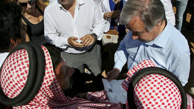 United Nations High Commissioner for Refugees (UNHCR) Antonio Guterres, right, reads an official paper for displaced Syrian men during his visit to a temporary refugee camp, in Deir al-Ahmar village, near Baalbek city, east Lebanon, on Tuesday, Sept. 16, 2014. Guterres and U.N. Development Program Administrator Helen Clark are visiting Lebanon to obtain a better understanding of the impact of the Syrian crisis in Lebanon, which hosts more than a million Syrian refugees, and discuss with authorities and donors the current response. (AP Photo/Hussein Malla)