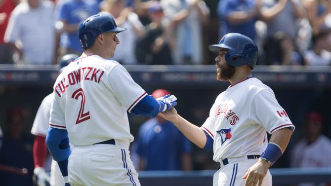 Toronto Blue Jays' Russell Martin, right, is congratulated by Troy Tulowitzki after hitting a two-run home run off Detroit Tigers pitcher Alfredo Simon during fourth-inning baseball game action in Toronto, Sunday, Aug. 30, 2015. (Chris Young/The Canadian Press via AP) MANDATORY CREDIT