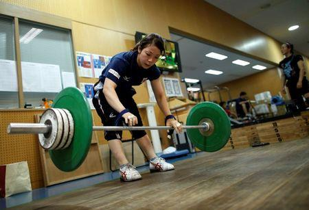 Japanese weightlifter and captain of Japan's athletes for the Asian Games Miyake works out at the National Training Center in Tokyo