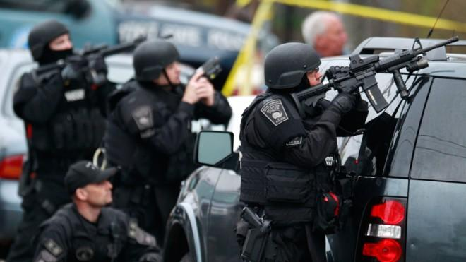 Police in tactical gear surround an apartment building in Watertown, Mass., April 19.