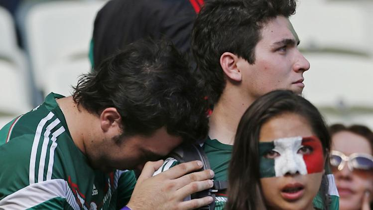 Mexican fans react after the World Cup round of 16 soccer match between the Netherlands and Mexico at the Arena Castelao in Fortaleza, Brazil, Sunday, June 29, 2014. The Netherlands won the match 2-1