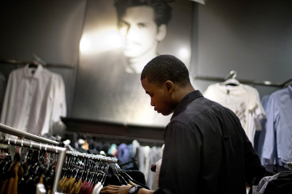 In this Wednesday, Dec. 12, 2012 photo, Dominic Plummer, of Atlanta, shops in an H&M store, in Atlanta. The Federal Reserve reports how much consumers borrowed in December on Thursday, Feb. 7, 2013.  (AP Photo/David Goldman)