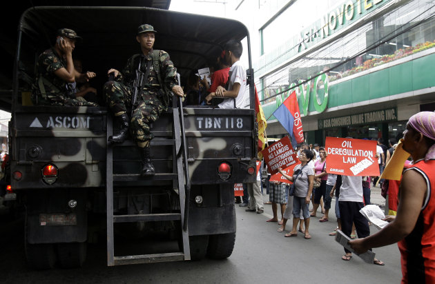 "A Philippine Army truck that offers free ride to commuters drives pasts protesters taking part in a nationwide ""transport holiday"" after continued oil price hikes in the past weeks in suburban Calooca"