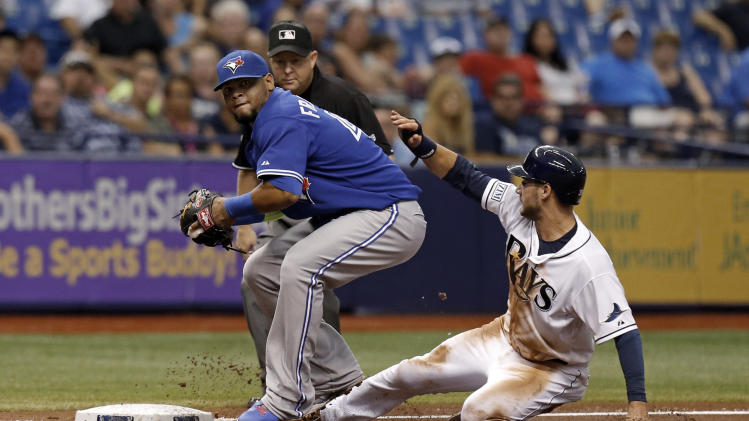 Toronto Blue Jays third baseman Juan Francisco forces Tampa Bay Rays' Kevin Kiermaier out at third on a ground ball by Matt Joyce as he looks to throw to first base while umpire Todd Tichenor looks on during the third inning of a baseball game Saturday, July 12, 2014, in St. Petersburg, Fla. (AP Photo/Mike Carlson)