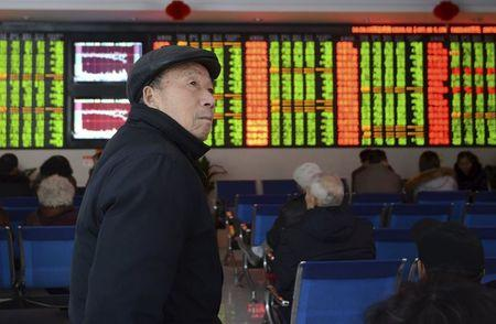 An investor looks on in front of an electronic board showing stock information at a brokerage house in Fuyang