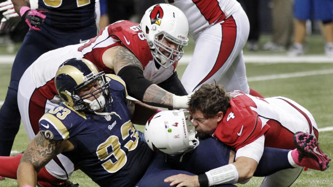 Arizona Cardinals quarterback Kevin Kolb, bottom right, is sacked by St. Louis Rams defensive tackle Jermelle Cudjo, bottom left, as Cardinals' Adam Snyder gets in on the play during the third quarter of an NFL football game, Thursday, Oct. 4, 2012, in St. Louis. Cudjo was charged with an unnecessary roughness penalty on the play. (AP Photo/Seth Perlman)
