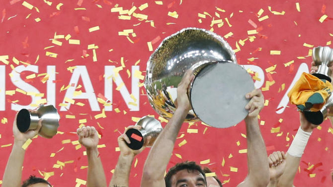 Australia's captain Mile Jedinak holds up the Asian Cup trophy as the team celebrate after winning their Asian Cup final soccer match against South Korea at the Stadium Australia in Sydney