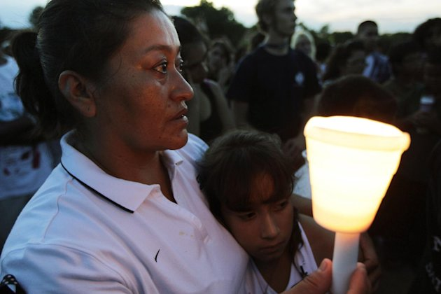 Maria Davila holds her daughter Alexia, 9, during a candle-light vigil, Friday, July 20, 2012, in Aurora, Colo., across the street from the movie theater where a gunman killed at least 12 people and w
