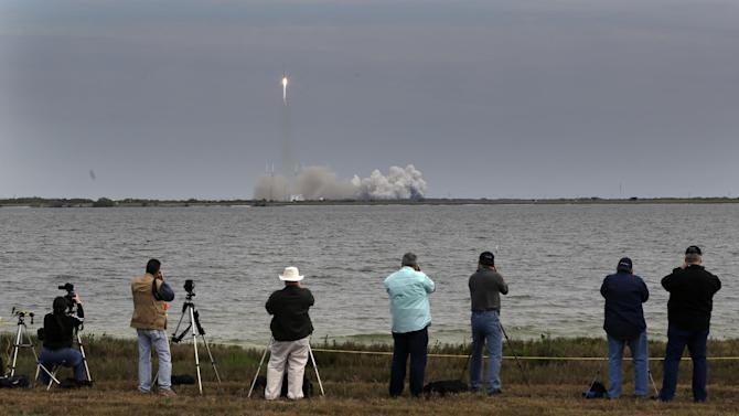 People photograph the Falcon 9 SpaceX rocket as it lifts off from launch complex 40 at the Cape Canaveral Air Force Station in Cape Canaveral, Fla. on Friday, March 1, 2013. The rocket is transporting the Dragon capsule to the International Space Station containing more than a ton of food, tools, computer hardware and science experiments. (AP Photo/John Raoux)
