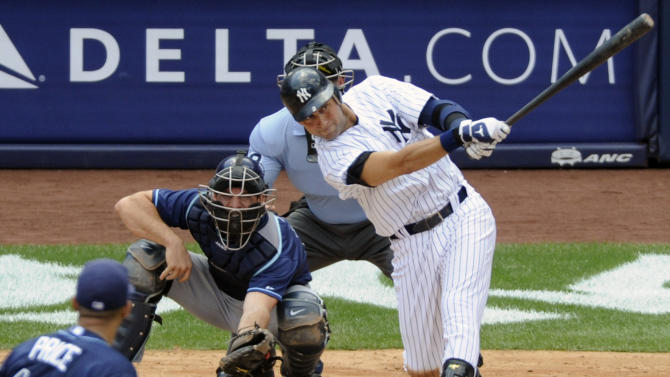New York Yankees' Derek Jeter follows through on a solo home run for his 3,000 career hit during the third inning of a baseball game against the Tampa Bay Rays Saturday, July 9, 2011 at Yankee Stadium in New York. Rays catcher John Jaso, pitcher David Price, left, and umpire Jim Wolf look on. (AP Photo/Bill Kostroun)