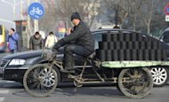 "A worker is seen delivering briquettes used for heating, in Beijing, on February. China has reached a ""turning point"" in its economic development, with the pace of growth likely to nearly halve in the next two decades, according to World Bank and Chinese government researchers"