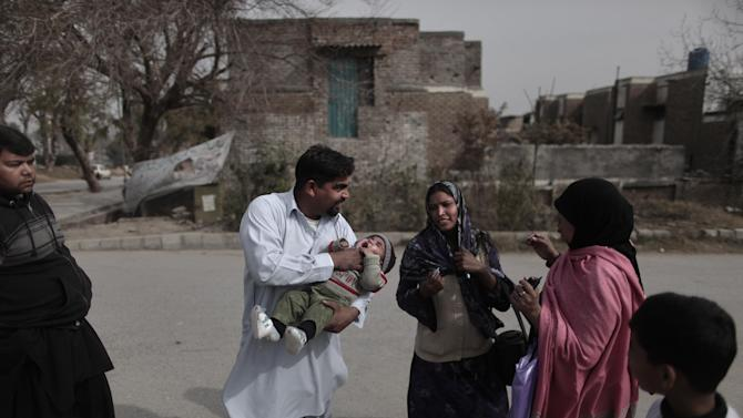 A Pakistani man holds his son as a health worker prepares to give the child a polio vaccine, in a neighborhood in Islamabad, Pakistan, Wednesday, Jan. 30, 2013.  Some Islamic militants oppose the vaccination campaign, accuse health workers of acting as spies for the U.S. and claim the polio vaccine is intended to make Muslim children sterile. Pakistan is one of the few remaining places where polio is still rampant. (AP Photo/Muhammed Muheisen)