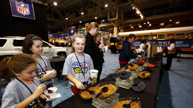 New Orleans children create their own bowl of oatmeal at the Quaker's NFL Experience in New Orleans on Wednesday, Jan. 30, 2013. (Jonathan Bachman / AP Images for Quaker Oats)