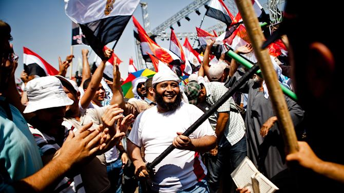 Supporters of Egypt's Islamist President Mohammed Morsi chant slogans and dance with sticks during a rally in Nasser City, Cairo, Egypt, Sunday, June 30, 2013. Thousands of opponents and supporters of Egypt's Islamist president began massing in city squares in competing rallies Sunday, gearing up for a day of massive nationwide protests that many fear could turn deadly as the opposition seeks to push out Mohammed Morsi. (AP Photo/Virginie Nguyen Hoang)