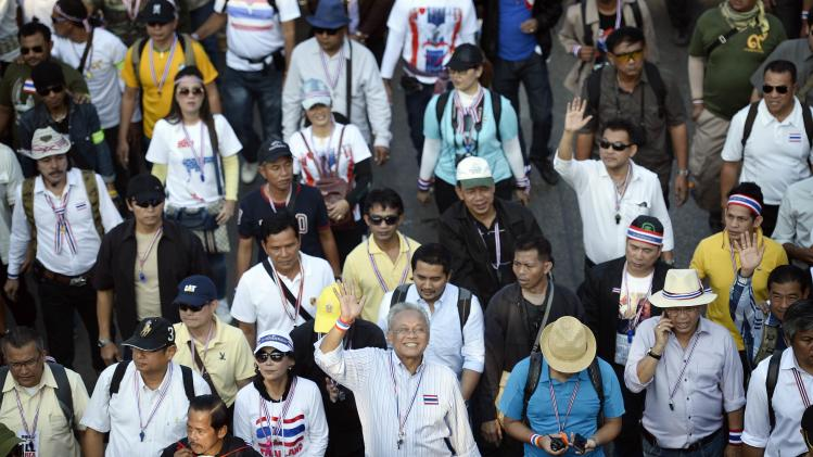 Protest leader Suthep Thaugsuban waves as he walks with anti-government protesters during a rally in Bangkok