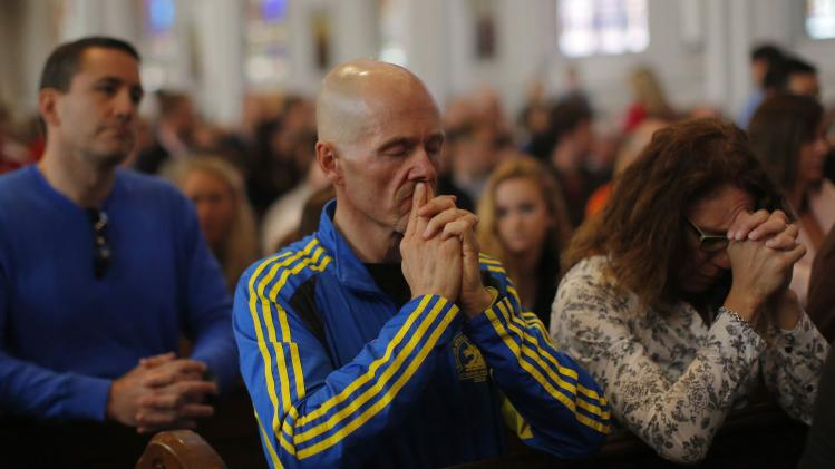 A 2014 Boston Marathon runner prays during Easter Mass at the Cathedral of the Holy Cross in Boston