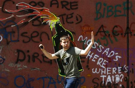A Turkish man gestures as he walks in front of a wall, spray-painted with anti-government graffiti, near Istanbul's Taksim square June 8, 2013. REUTERS/Yannis Behrakis