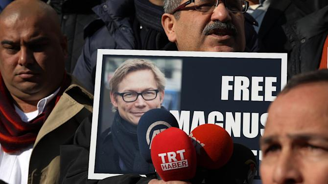 FILE - In this Monday, Dec. 23, 2013 file photo, a Turkish journalist holds a placard with a photo of Magnus Falkehed, a Swedish correspondent based in Paris, who was abducted in Syria in November 2013 by armed Syrian opposition groups, during a protest in Ankara, Turkey. On Wednesday, Jan. 8, 2014, Sweden's Foreign Ministry confirmed the release of writer Magnus Falkehed and photographer Niclas Hammarstrom, and said both were receiving assistance from Swedish diplomats in Beirut. (AP Photo/Burhan Ozbilici, File)