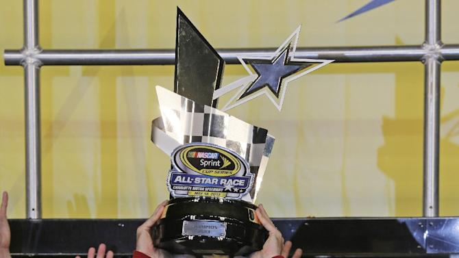 Jimmie Johnson raises the trophy in victory lane with his wife Chandra, right, after winning the NASCAR All-Star auto race at Charlotte Motor Speedway in Concord, N.C., Saturday, May 18, 2013. (AP Photo/Chuck Burton)