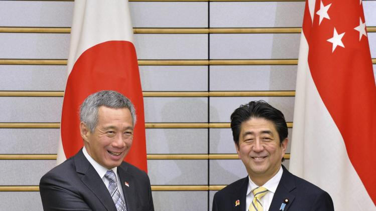 Singapore's Prime Minister Lee shakes hands with Japanese counterpart Abe at the start of their talks in Tokyo