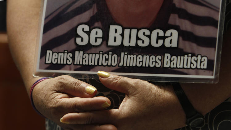 "FILE - In this Oct. 28, 2012 file photo, a member of a caravan of Central American mothers hold a photograph of her disappeared child during a Mass at the Basilica of Guadalupe in Mexico City. The sign reads in Spanish ""Looking for Denis Mauricio Jimenes Bautista."" A new Human Rights Watch report released on Wednesday, Feb. 20, 2013 calls Mexico's anti-drug offensive ""disastrous"" and cites 249 cases of disappearances, about 149 of which include evidence of being carried out by the military or law enforcement. The report says the forced disappearances follow a pattern in which security forces detain people without warrants at check-points, homes, workplaces or in public. Human Rights Watch criticizes former President Felipe Calderon for ignoring the problem, calling it ""the most severe crisis of enforced disappearances in Latin America in decades."" (AP Photo/Marco Ugarte, file)"