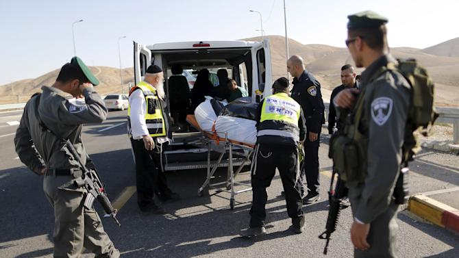 Israeli emergency personnel evacuate the body of a Palestinian, who Israeli police and military said rammed his vehicle into Israeli soldiers, in the occupied West Bank