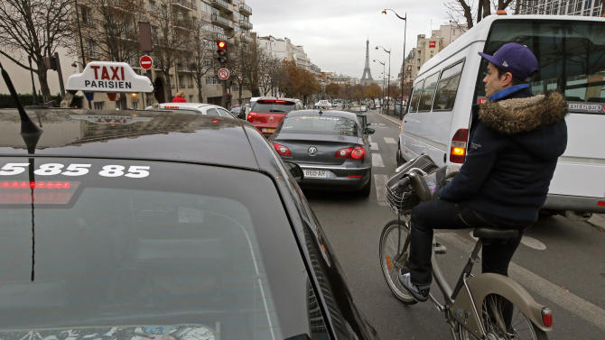 "Johan Maige from Paris, rides a Velib bike-sharing program between cars in Paris, Tuesday, Oct. 30, 2012. From London's ""cycle superhighways"" to popular bike-sharing programs in Paris and Barcelona, growing numbers of European cities are embracing cycling as a safe, clean, healthy, inexpensive and even trendy way to get around town. (AP Photo/Francois Mori)"