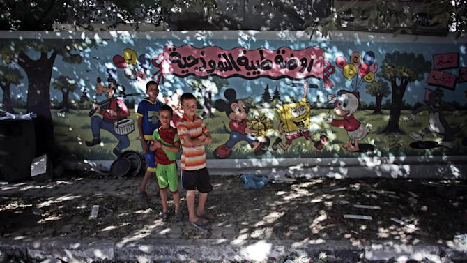 """Palestinian boys stand next to wall with murals and Arabic writing that reads """"Tiba standard nursery,"""""""