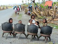 Children wait for relief goods in the southern town of New Bataan on December 12, 2012. Residents of New Bataan, which suffered over 500 dead, are still struggling to recover, building makeshift shelters out of scrap wood and rags