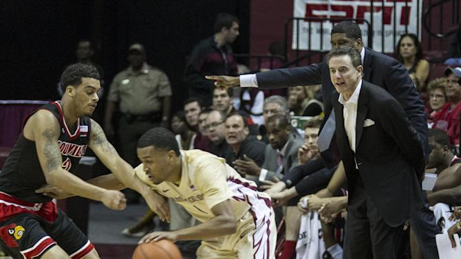 Louisville head coach Rick Pitino, right, watches as Florida State's Devon Bookert drives around Louisville's Quentin Snider in the first half of an NCAA college basketball game in Tallahassee, Fla., Saturday, Feb. 28, 2015. (AP Photo/Mark Wallheiser)