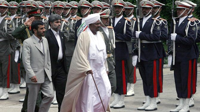 FILE - Sudanese President Omar al-Bashir, center, and Iranian President Mahmoud Ahmadinejad, left, review an honor guard, in Tehran, Iran, in this Wednesday, April, 26, 2006 file photo. Explosions at a military site near Sudan's capital Khartoum on Oct 23 2012, widely believed to be the result of an Israeli airstrike, point to a possible escalation in a hidden front of the rivalry between  Iran and Israel which believes arms pipeline through Sudan to Islamic militants on Israel's borders.  (AP Photo/Hasan Sarbakhshian, file)