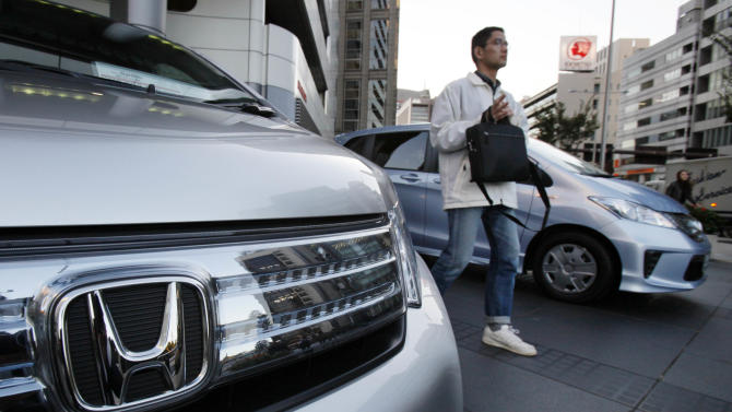 A man walks by Honda vehicles displayed in front of Honda Motor Co. headquarters in Tokyo Monday, Oct. 29, 2012. Honda's quarterly profit surged 36 percent as Japanese automakers bounced back from last year's tsunami disaster in northeastern Japan, but the company lowered its annual forecasts Monday because of a sales plunge in China. (AP Photo/Koji Sasahara)