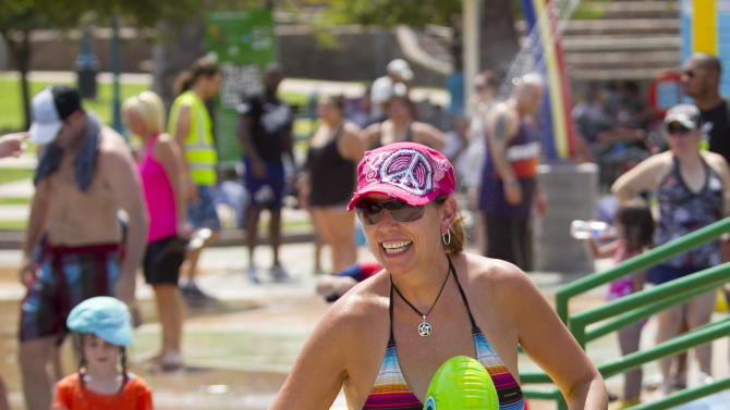 Kim Roer smiles as she cools off at the splash pad at Tempe Beach Park during the Tempe Bicycle Action Group swimsuit ride in Tempe, Ariz. on Saturday, June 29, 2013. About 100 biked around the city cooling off in splash pads, pools and fountains. (AP Photo/The Arizona Republic, David Wallace)